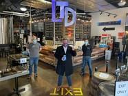 Commissioner LaTondresse standing inside LTD Brewing alongside staff