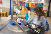 Girl putting recycling into waste station in school cafeteria