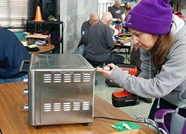 Woman with screwdriver repairing a toaster oven