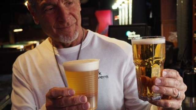 Bartender at Park Tavern holds up plastic cup and glass filled with beer