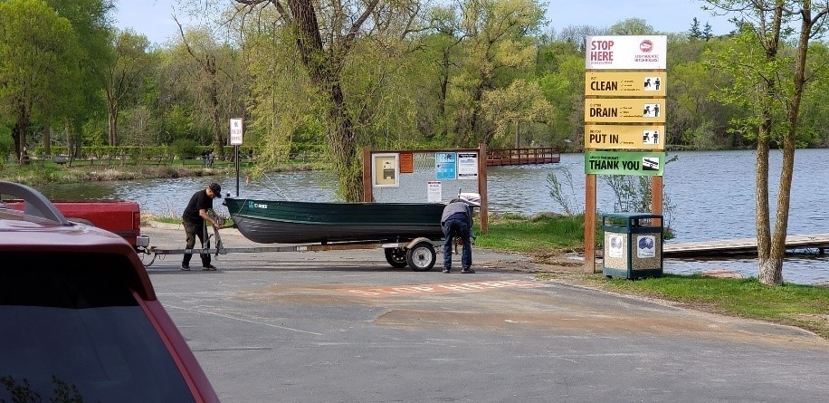 Boaters putting in at public access with aquatic invasive species prevention signage