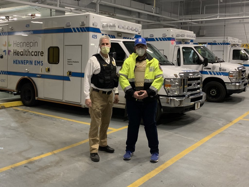 Two men stand near EMS vehicles