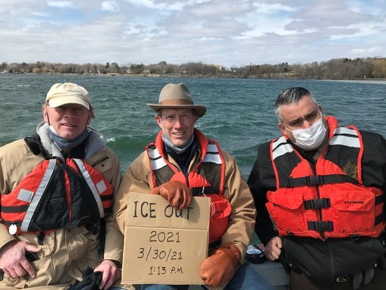 Three people wearing life jackets on Lake Minnetonka with sign declaring ice out