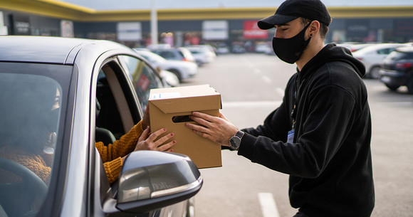 Man in mask handing a box to a woman in a car