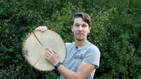 Forester pointing at growth rings on a tree cutting