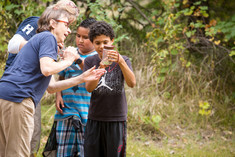 Two women naturalists looking at bugs in a jar with two students