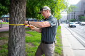 Man measuring tree with a measuring tape wrapped around tree at chest height