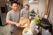 Man scraping food scraps from cutting board into organics bin