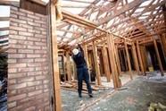 Person taking apart house lumber walls
