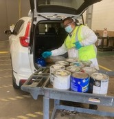 Staff at drop-off facilities wearing a mask and unloaded materials from car