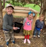 Kids standing in front of compost bin