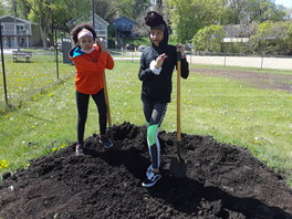 Two girls with shovels standing on garden bed with compost