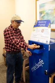 Man putting medicine into a medicine drop box
