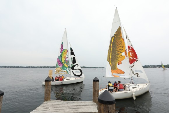 Two sailboats with colorfully painted sails to featuring fish to raise awareness about aquatic invasive species
