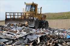 Front end loader moving waste on top of a landfill