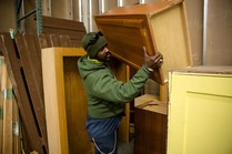 Man stacking cabinets to be sold in reuse warehouse