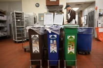Bin set up in commercial kitchen with trash, recycling, and organics recycling