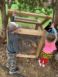 Kids adding food scraps to a backyard compost bin