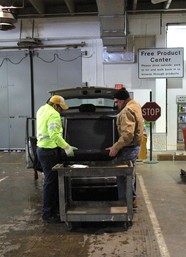 Staff and resident unloading a TV from the back of a car at a drop-off facility