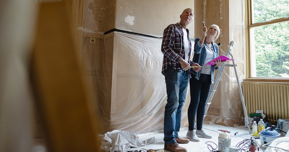 Man and woman having a discussion in a room under construction