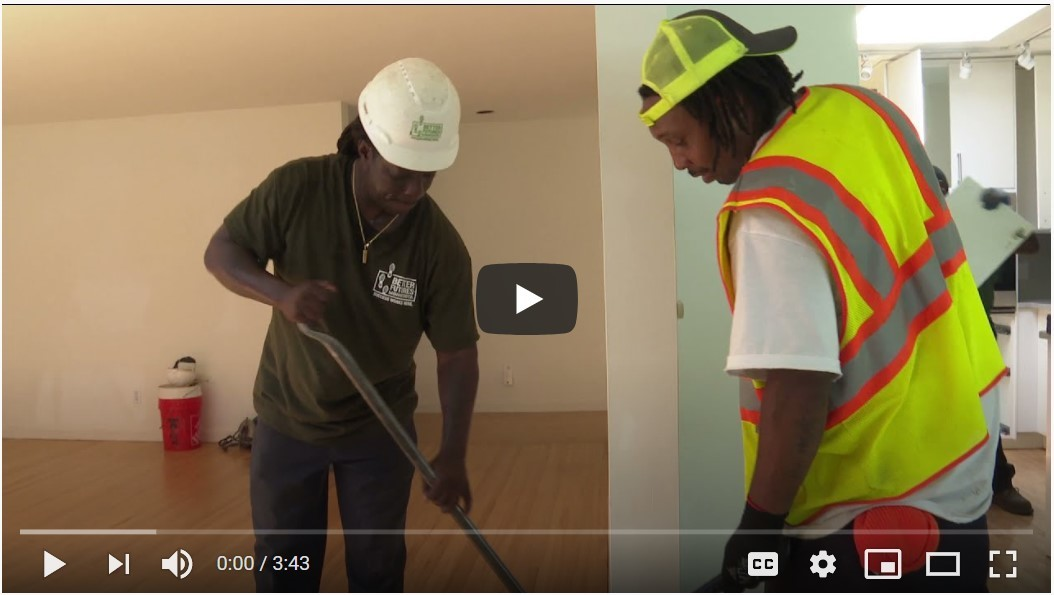 Screenshot of video with two men working on deconstructing a house using hand tools