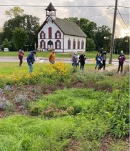 A group of people in a rain garden outside of a church