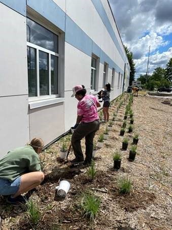 Woman with a shovel helping to plant a rain garden outside the Regional Apprenticeship Training Center