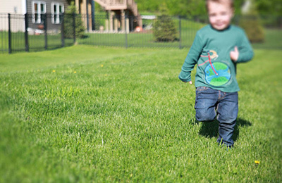 Boy running through green lawn wearing shirt with bicycle and earth as the wheel