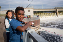 Two kids fishing on deck overlooking Coon Rapids Dam on the Mississippi River