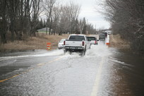 Cars driving over a flooded road with water running over it