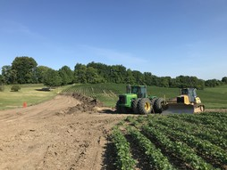 Earth moving equipment install erosion control practices in a farm field