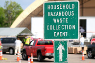 Sign that says hazardous waste collection events with people dropping off materials in background