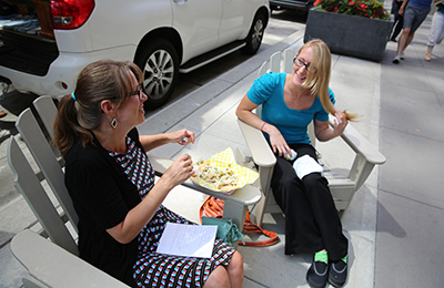 Two people sitting in chairs on a sidewalk having a conversation