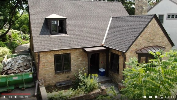 Screenshot of Edina deconstruction video showing old brick home with dumpster full of materials outside
