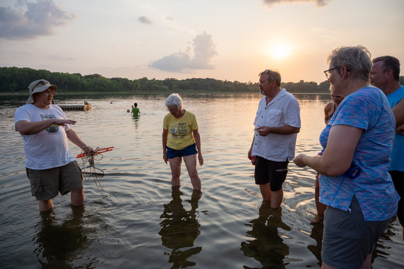 People in ankle deep water learning about AIS