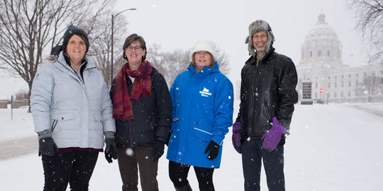 Snow falling as Kim, Kris, JoAnn, and Jay stand in front of the Minnesota State Capitol Building.