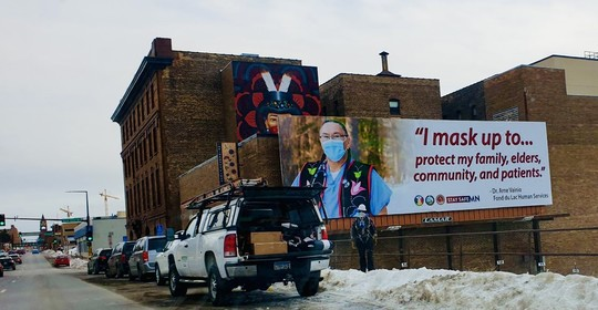 "Billboard with a person and the quote ""I mask up to protect my family, elders, community, and patients."""