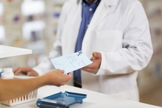 person at pharmacy handing the pharmacist a doctors perscription note.