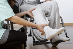 person in a wheelchair receiving physical therapy.