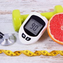 Blood glucose monitor, stethoscope, dumbell, measuring tape, and grapefruit.