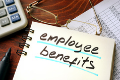 """""""Employee Benefits"""" written on a notepad on an office desk."""