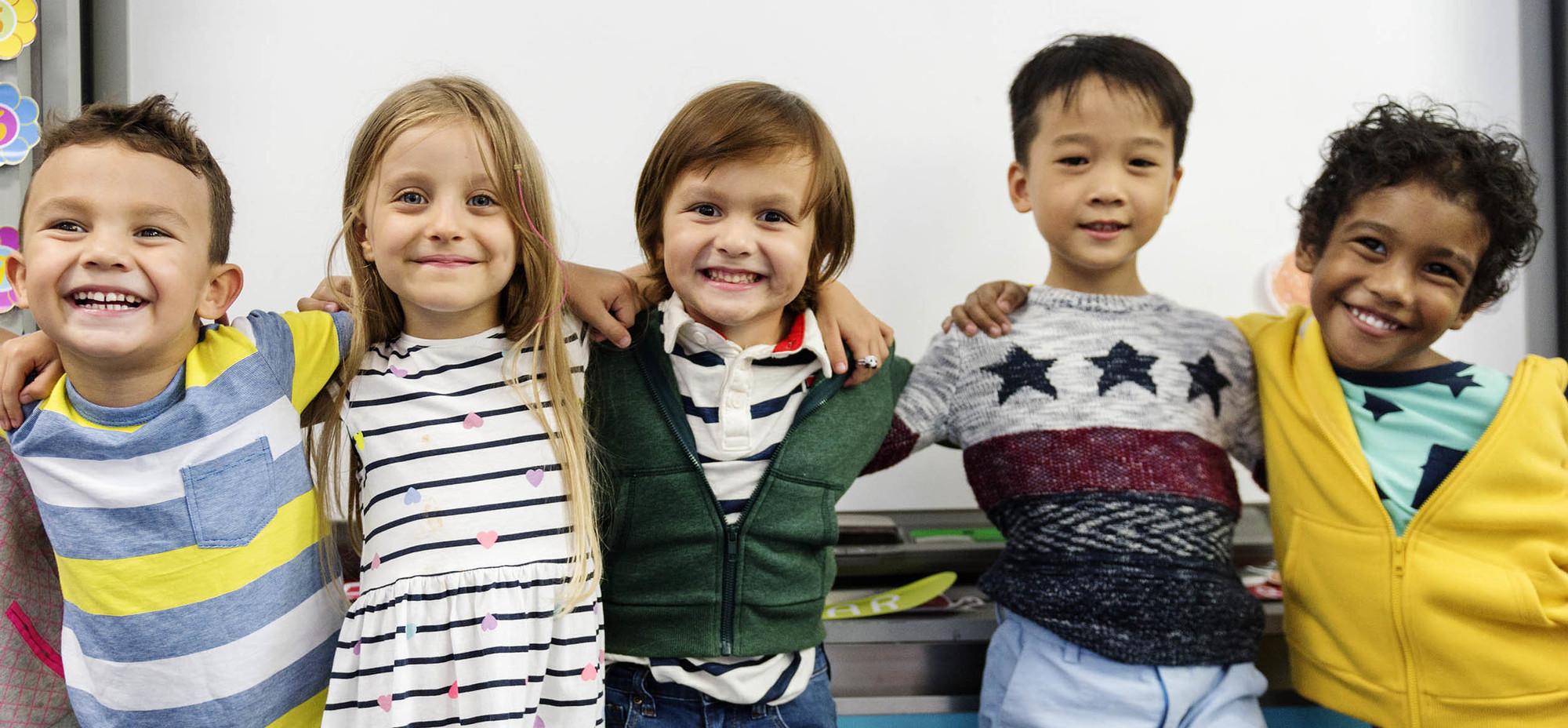 Photo of diverse group of kindergartners hugging