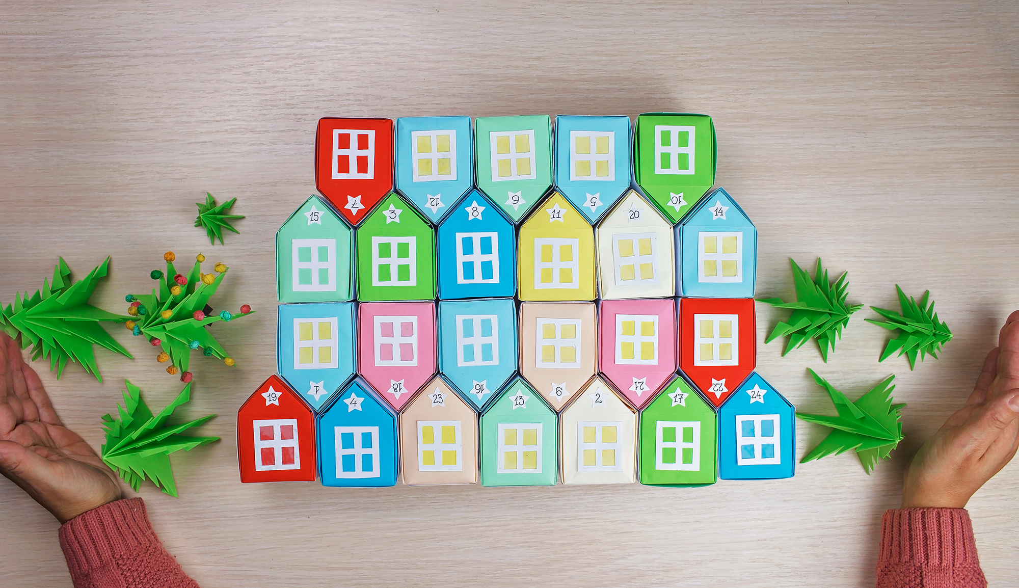 Photo of child's hands with colorful crafted Christmas miniature houses