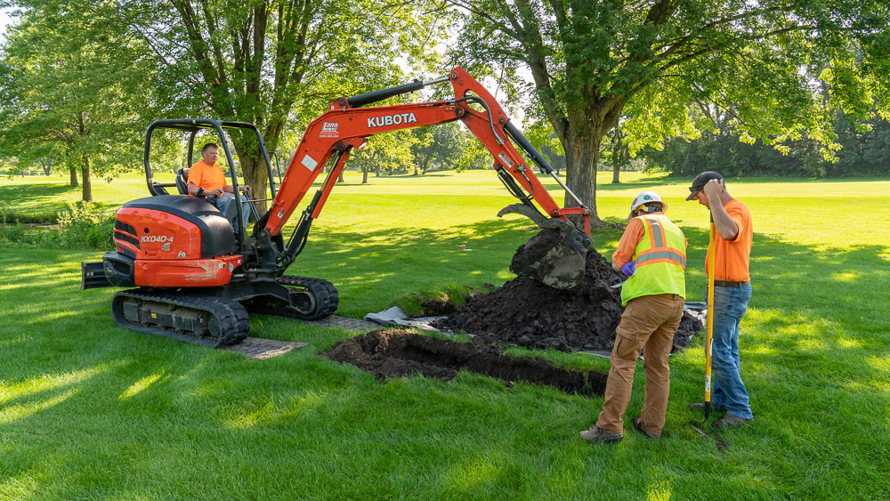 Contractors using an excavator to dig a test pit at the Columbia Golf Course.