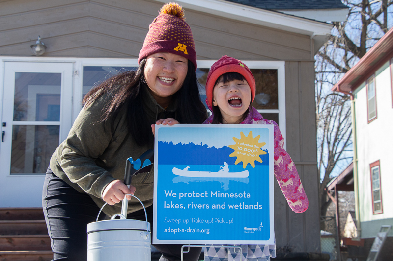 A woman and a young girl pose with an Adopt-A-Drain sign.