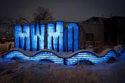 MWMO sign sculpture at night.
