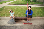 A woman and child sit next to a cleaned stormdrain.