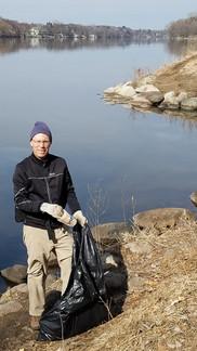 A volunteer picking up trash along the Mississippi River.
