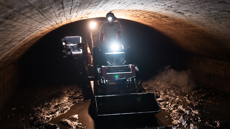 Worker operating a skidloader in a tunnel.
