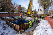 Workers installing parts of a hydrodynamic separator beneath 35th Avenue in Northeast Minneapolis.